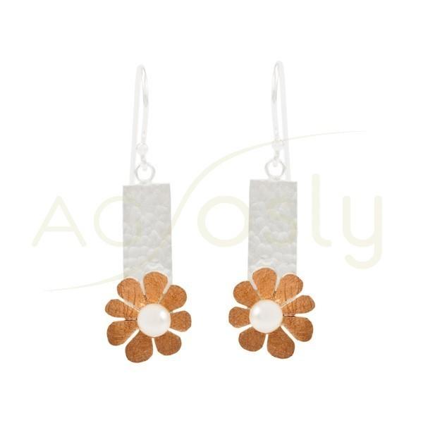 Pendientes de plata en forma de flor con una perla central, con detalles dorados y cierre de gancho.
