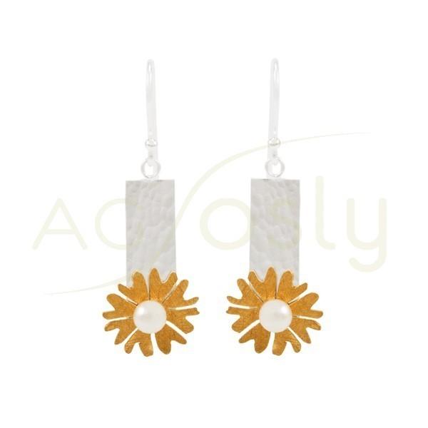 Pendientes de plata en forma de flor con una perla central, con detalles dorados, y cierre de gancho.